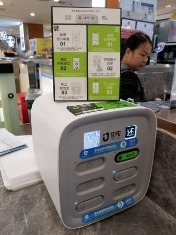 Caja de baterías externas de Ankerbox en un puesto de pasteles junto a una estación de metro.