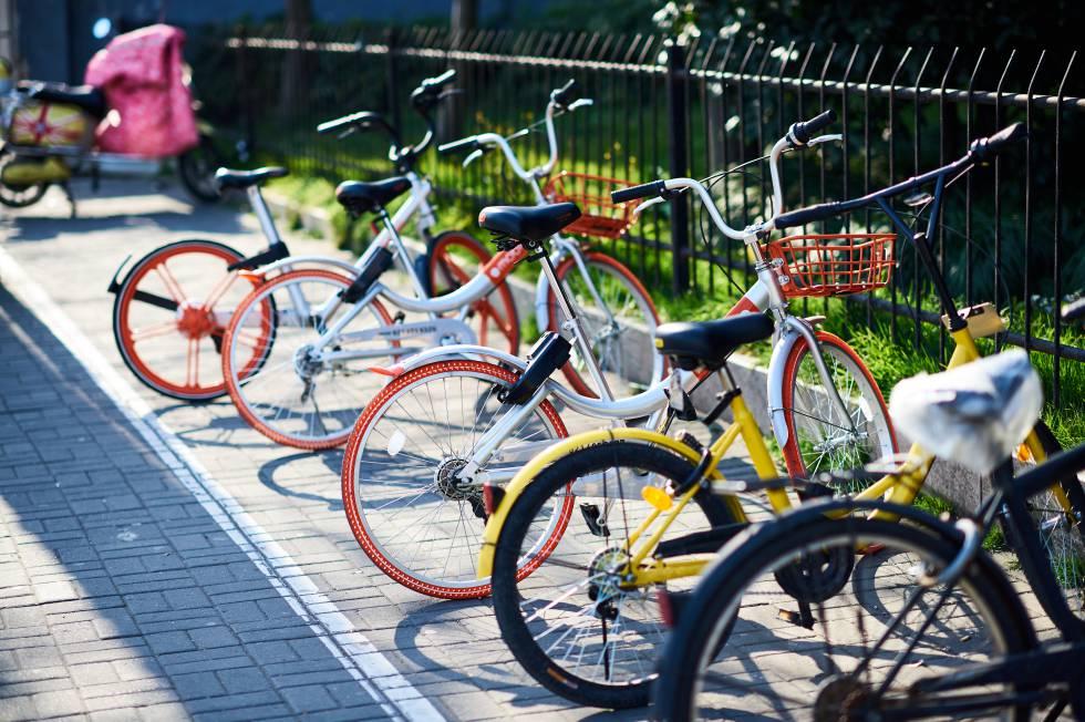 Una bici Ofo (amarilla) y varias Mobike esperan ser usadas por alguien en una calle de Shanghái.