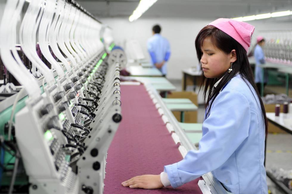 Una trabajadora toca la tela de la fábrica textil automatizada de Antex en Hangzhou.