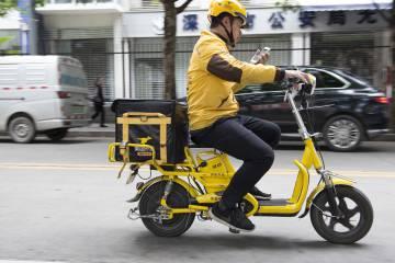 Un mensajero de Waimai comprueba la dirección a la que lleva comida a domicilio a bordo de una bicicleta eléctrica.