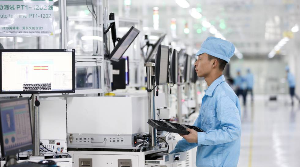 An employee reviews the production process of the smartphones.